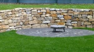 Trockene Natursteinmauer mit Grillplatz mit Kopfsteinpflaster